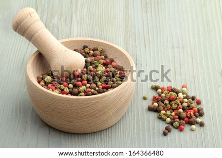 mortar and pestle with peppercorn mix on wooden table