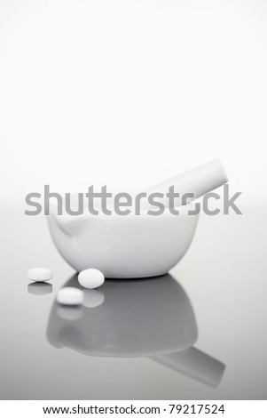 Mortar and pestle with pills against a white background - stock photo