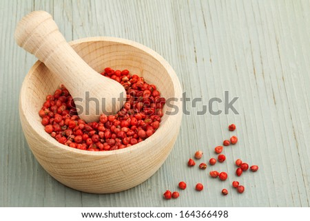 mortar and pestle with red peppercorns on wooden table - stock photo
