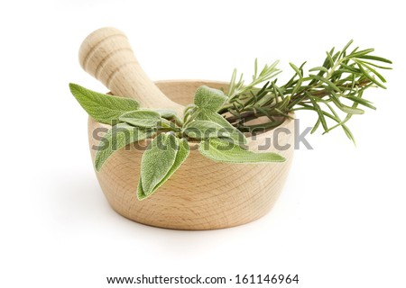 mortar and pestle with sage and rosemary - stock photo