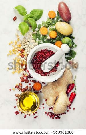Mortar and pestle with various colorful spices and vegetables on marble table . Cooking, healthy or vegetarian eating concept. - stock photo