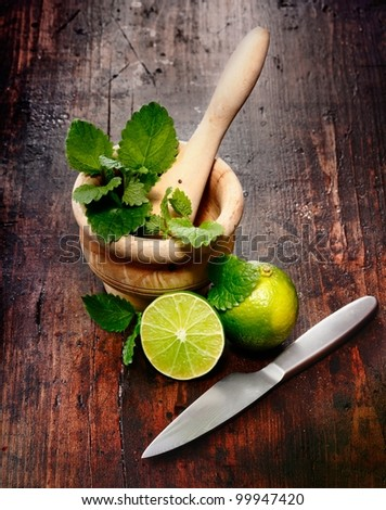 Mortar, Limes and Peppermint on a wood Background. Ingredients for Caipirinha and Mojito Cocktails and other drinks - stock photo