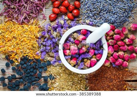Mortar of healing herbs, herbal tea assortment and berries on table. Top view. Herbal medicine. - stock photo
