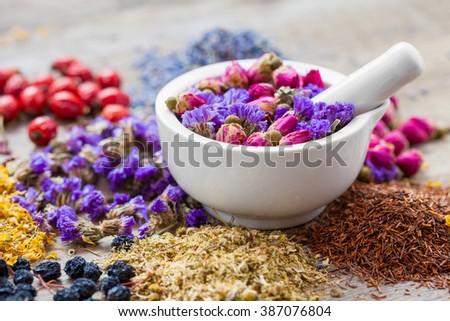 Mortar of healing herbs, herbal tea assortment and dry berries on table. Herbal medicine. - stock photo