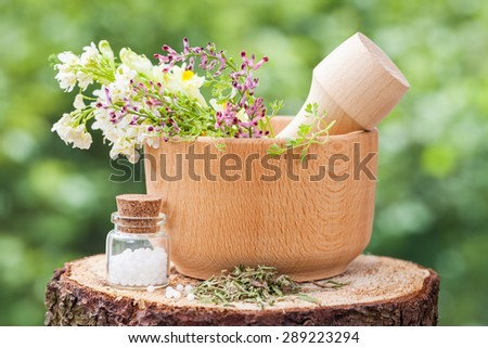 Mortar with healing herbs and bottle of homeopathy globules on wooden stump outdoors. - stock photo