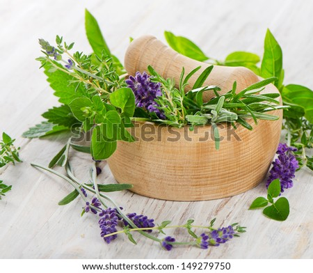 Mortar with  herbs on a wooden table. Selective focus