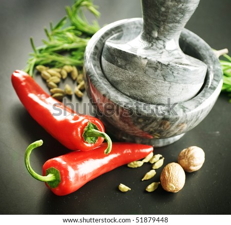 Mortar with pestle, Herbs and Spices.Over black background