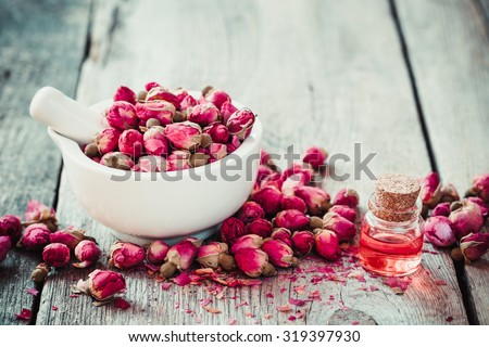 Mortar with rose buds and essential roses oil. Selective focus. - stock photo
