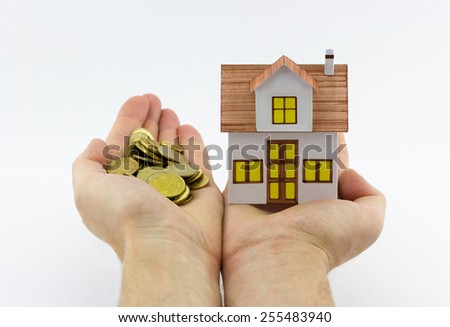 Mortgage concept. Close-up view of man holding small toy house in one hand and golden coins in the another hand on white background - stock photo