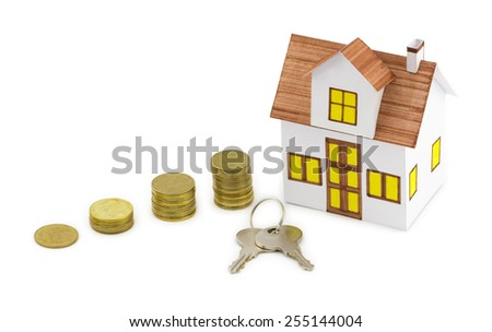 Mortgage concept. Close-up view of small toy house with keys and golden coins isolated on white background