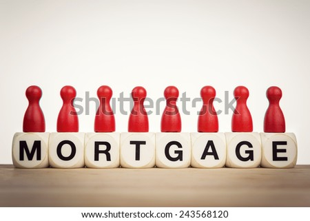 Mortgage concept: Red pawns on the word mortgage spelled by toy dice - stock photo