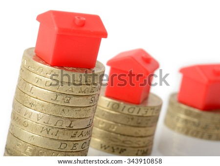 Mortgage concept small houses on stacks of coins - stock photo