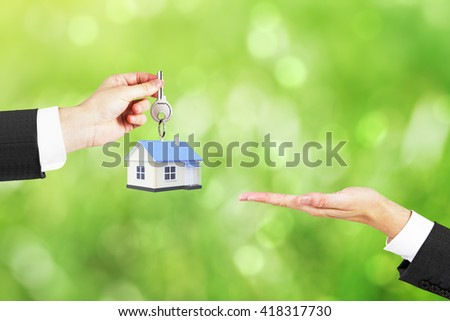 Mortgage concept with businessman handing house with key to another man on abstract green background