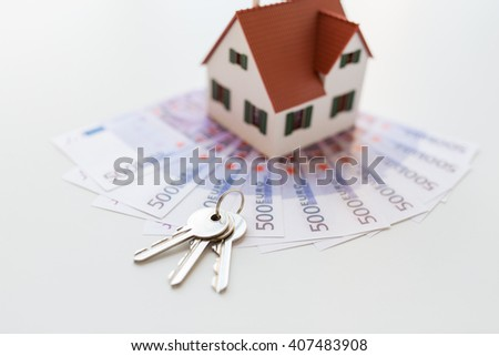 mortgage, investment, real estate and property concept - close up of home model, money and house keys - stock photo