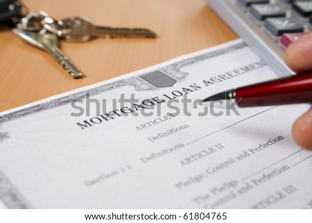 Mortgage loan agreement on the desk with pen on human hand - stock photo