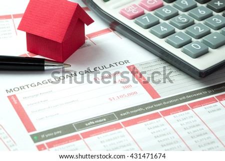 Mortgage loan balance sheet with a miniature ed paper house and calculator
