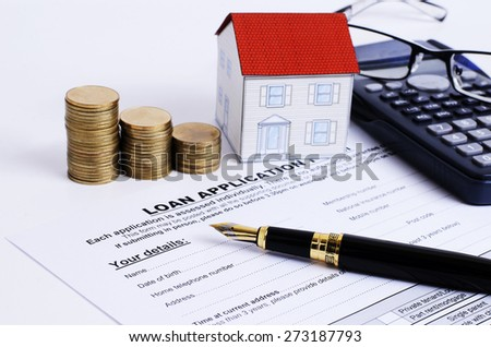 Mortgage loans concept with close up fountain pen and loan application form and coins stack and paper house and eyeglasses on calculator