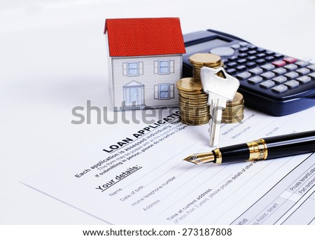 Mortgage loans concept with Fountain pen and key and calculator and paper house and coins stack on Loan Application form - stock photo