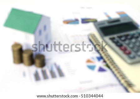 Mortgage loans with coins and paper house on offices desk Blurred backgrounds