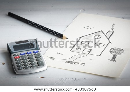 Mortgage or loan concept. A drawing of a house and calculator. - stock photo