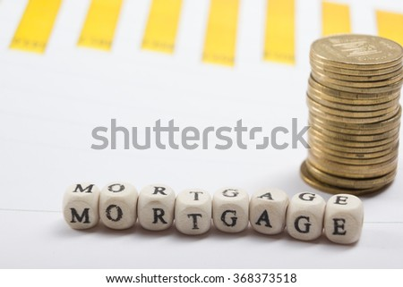 MORTGAGE word written on wood block, golden coins and chart - stock photo