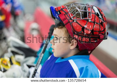 MOSCOW - APR 28: A young hockey player in stylish helmet on closing ceremony of championship season of 2011-2012 Ice Hockey for Sports School, junior teams on April 28, 2012, Sokolniki, Moscow, Russia - stock photo