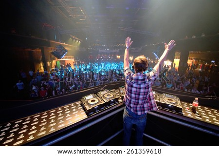 MOSCOW - APR 05, 2014: DJ in a plaid shirt with his arms raised spinning the decks at the Trancemission in Stadium Live, view from the back - stock photo