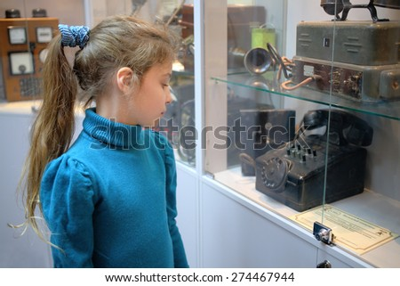 MOSCOW - APR 05, 2014: Girl examines vintage telephone exhibits in the Museum of the History telephone in Moscow