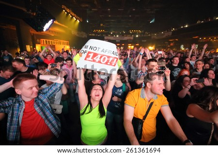 MOSCOW - APR 05, 2014: Happy young people with placards and mobile phone the Trancemission in Stadium Live - stock photo