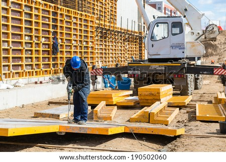 MOSCOW - APRIL 24: Construction site worker on april 24, 2014 in Moscow, Russia. Urban construction is at a faster pace in Russia. - stock photo