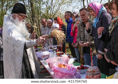 MOSCOW - APRIL 30, 2016: Orthodox priest spatter the holy water of Easter cakes at the celebration of Orthodox Easter by the church of St. Nicholas in Moscow. - stock photo