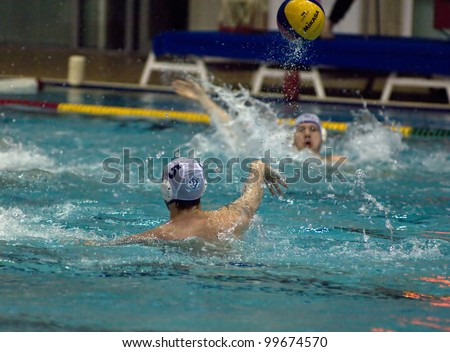 MOSCOW - APRIL  6: Shepelev R. gives a pass during a game Dynamo(white) vs Sintez (green) of waterpolo Championship of Russia on April 6, 2012 Moscow, Russia. Sintez won 11:10 - stock photo