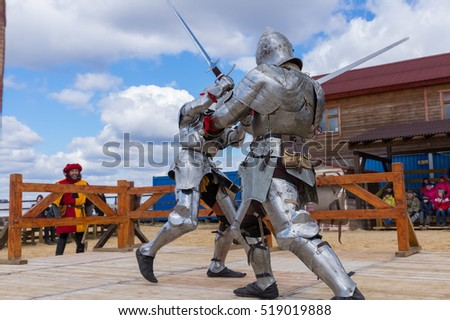 MOSCOW - APRIL 2016: Two armored swordsmen dressed as knights fight with swords at knight tournament reconstruction