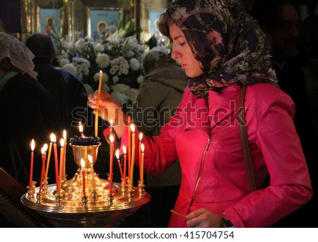 MOSCOW - APRIL 30, 2016: Unidentified woman light a candle at the celebration of Orthodox Easter by the church of St. Nicholas in Moscow. - stock photo