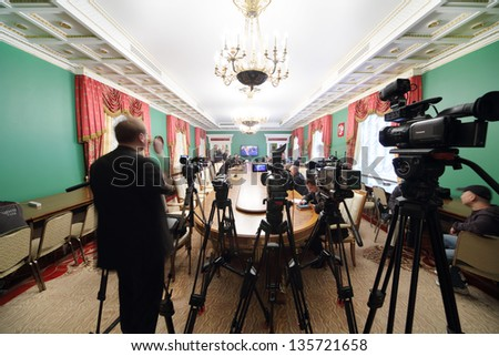 MOSCOW - APRIL 24: Video cameras and newspapermans sit in front of TV on Enlarged meeting of Council in Grand Kremlin Palace on April 24, 2012 in Moscow, Russia. - stock photo