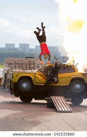 MOSCOW - AUG 25: Stuntman flies over the burning car on Festival of art and film stunt Prometheus in Tushino on August 25, 2012 in Moscow, Russia. The festival was organized in 1998. - stock photo