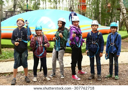 MOSCOW, AUGUST 18, 2015: Children in safaty equipment ready to pass difficult climbing route in special park for sport activities, Moscow, August 18.