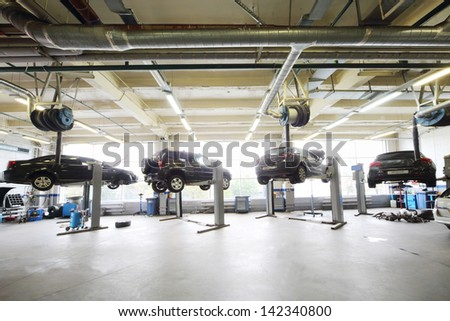MOSCOW - AUGUST 28: Four black cars raised on lifts in garage Avtomir on Baykalskaya, on August 28, 2012 in Moscow, Russia. Avtomir Group - large car dealer in Russia. - stock photo