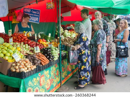 MOSCOW - AUGUST 08: People buying vegetables in Vegetable Fair on Leskov Street on August 8, 2014 in Moscow. - stock photo