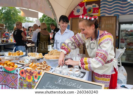MOSCOW - AUGUST 24: Saleswoman dressed in national costume selling apples during Apple Feast Day in VDNKH on August 24, 2014 in Moscow. Savior of Apple Feast Day is an Eastern Slavic folk holiday. - stock photo