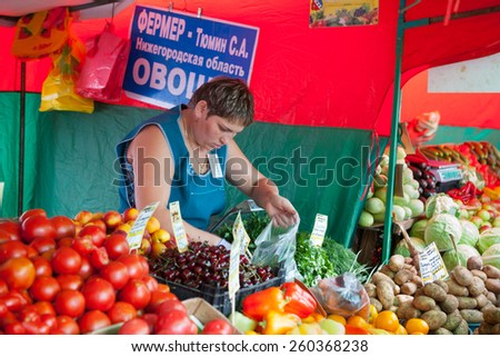 MOSCOW - AUGUST 08: The saleswoman selling fruit in Vegetable Fair on Leskov Street on August 8, 2014 in Moscow. - stock photo