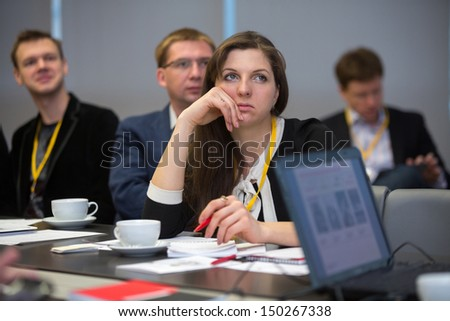 MOSCOW - DEC 20: The girl sits at a table and listen to the speaker on Business Breakfast at the office Rosbank on December 20, 2012 in Moscow Russia. - stock photo