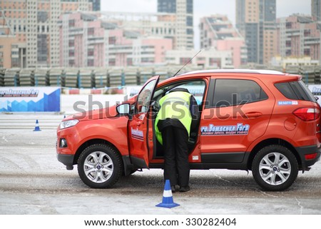 MOSCOW - DEC 05, 2014: The instructor checks the car at the opening of the Academy of safe driving Ford in Moscow