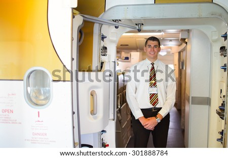 MOSCOW - DECEMBER 10, 2014: handsome Emirates crew member meet passengers. Emirates handles major part of passenger traffic and aircraft movements at the airport. - stock photo
