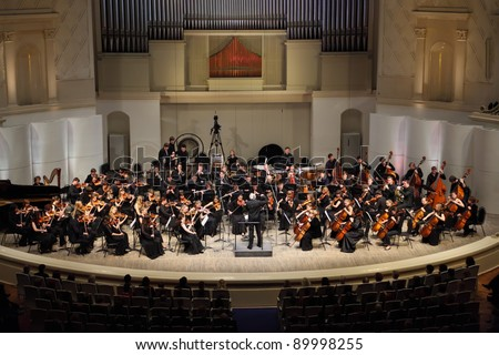 MOSCOW - FEBRUARY 26: Conductor Anatoly Levin directs Symphony Orchestra of Moscow State Conservatory named after P. Tchaikovsky in Tchaikovsky Concert Hall, on February 26, 2011 in Moscow, Russia. - stock photo