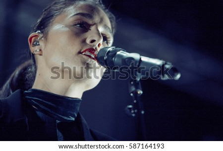 MOSCOW - 16 FEBRUARY,2015: Popular British pop singer Jessie Ware sing on stage in microphone.Stylish young woman singing on scene.Bright concert scene lighting,late night adult entertainment event