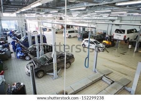 MOSCOW - JAN 11: Mechanics repair cars in station for maintenance in Center Varshavka on January 11, 2013, Moscow, Russia. Official dealer of Volkswagen Varshavka Center opened in 2010 - stock photo