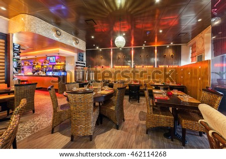 "MOSCOW - JULY 2014: Interior of a luxury restaurant""OGNI"". Main room with tables, wicker furniture, wine rack, modern bar made of wood"