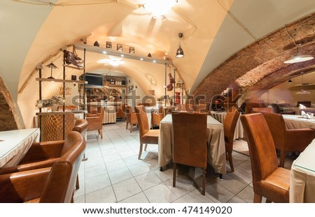 "MOSCOW - JULY 2014: Interior of beer restaurant ""CAPITAL"" located in an old basement with brick arches. Hall with tables and leather chairs"