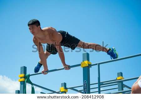 MOSCOW - JULY 26: Unidentified athlete performs during the street workout championship at Moscow City Games in Luzhniki on July 26, 2014 in Moscow. - stock photo
